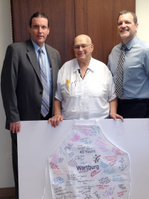 (L to R) Chuck Fox, Senior Director of Food Services for Morrison Senior Living, Frank Sciarpelletti, Wartburg Head Cook and David J. Gentner, Wartburg President and CEO, pose with honorary apron presented to Mr. Sciarpelletti for 40 years of dedicated service to Wartburg.